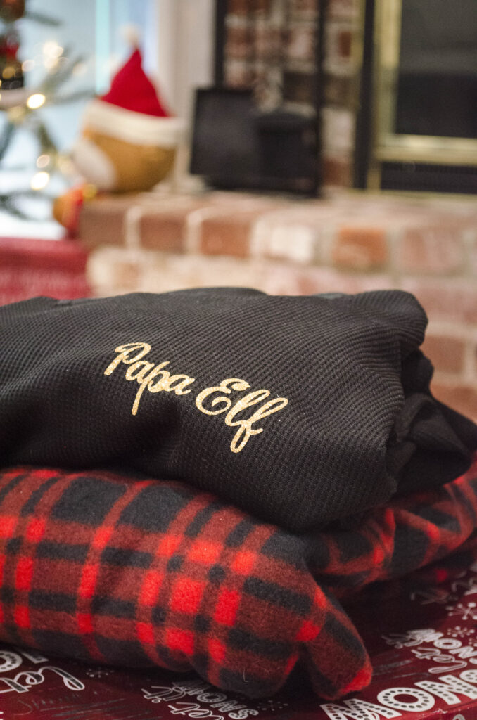 Black 'Papa Elf' shirt stack on plaid blanket on top of Christmas presents
