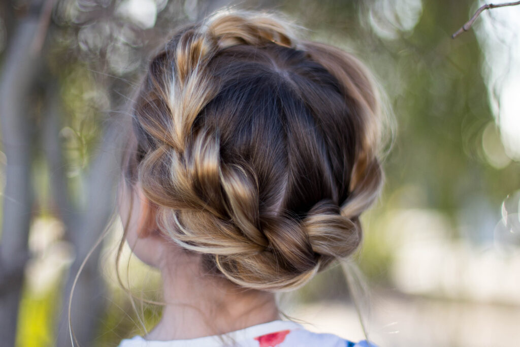 "Close up back view of young girl outside modeling ""Pull-Thru Crown Braid"" hairstyle"