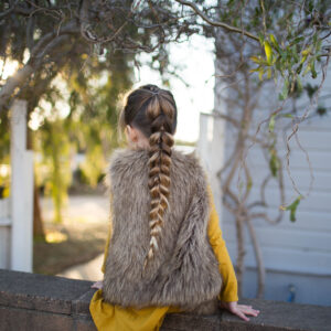 "Back view of girl wearing faux fur vest over yellow dress outside modeling the ""Dutch Pull-Thru Combo Braid"" hairstyle"