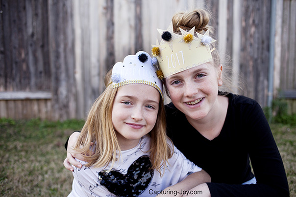 Two young girls outside playing while wearing 'DIY' New Years Eve crowns