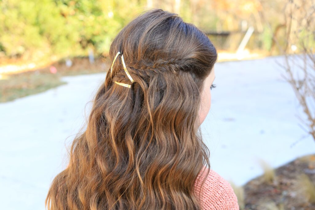 """Side view of a young girl outside with long hair modeling """"Barrette Tieback"""" hairstyle"""