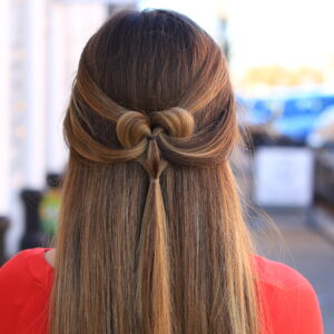 "Back view of girl outside wearing a red shirt modeling ""The Pancaked Heart"" hairstyle"