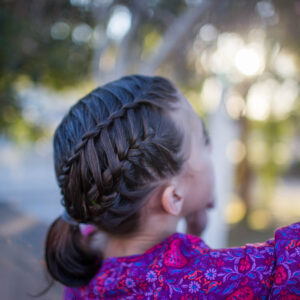 "Side view of a young girl playing outside modeling ""Gym Braid Combo"" hairstyle"