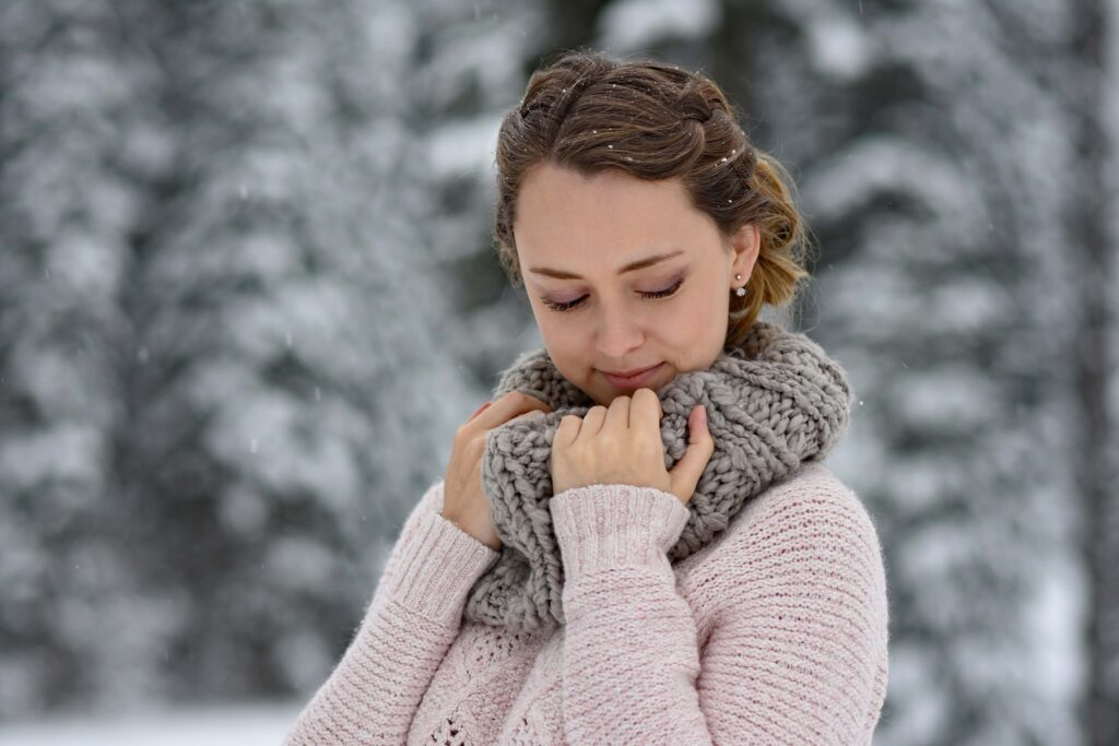 "Side view of girl standing outside in the snow while holding her scarf and modeling "" Double French Buns"" hairstyle."