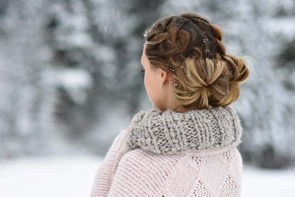 "Back view of girl standing outside in the snow while holding her scarf and modeling "" Double French Buns"" hairstyle."