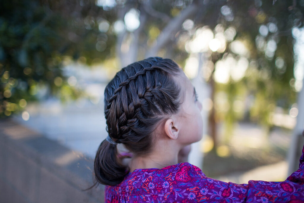 """Side view of a young girl playing outside modeling """"Gym Braid Combo"""" hairstyle"""
