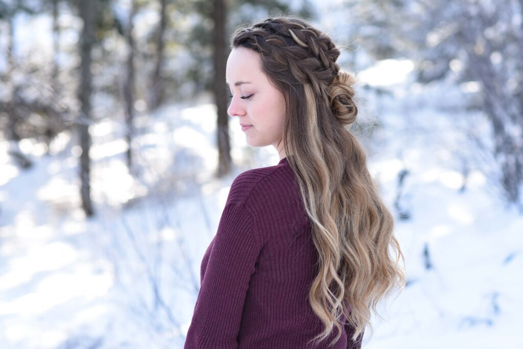 "Profile of girl looking down while standing outside in a snowy forest modeling the ""Double Dutch Half-Up"" hairstyle"