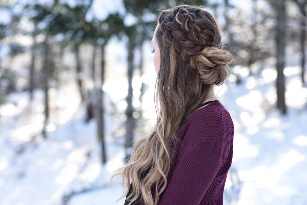 "Side view of girl standing outside in a snowy forest modeling the ""Double Dutch Half-Up"" hairstyle"