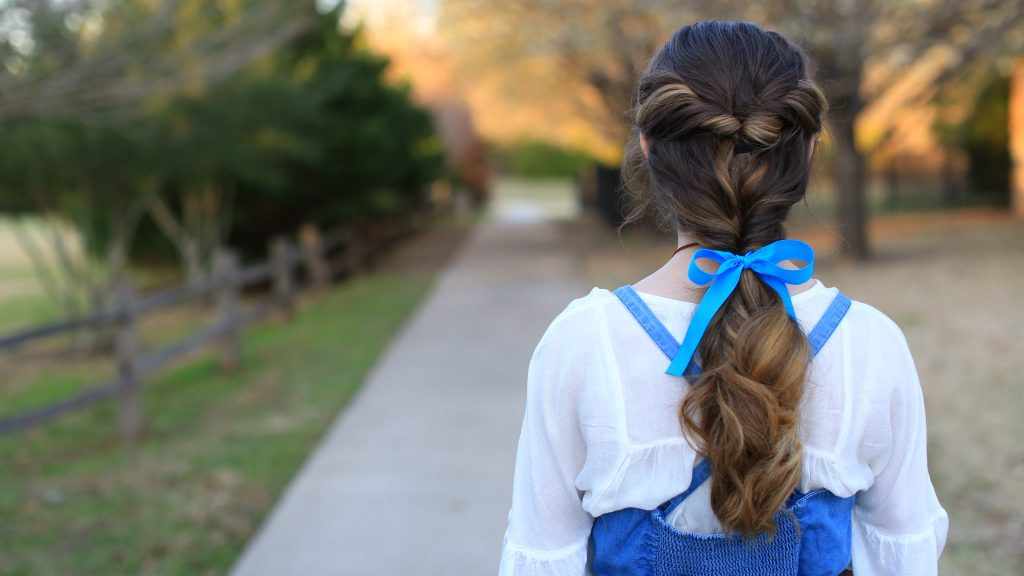 "Back view of young girl with long in Halloween costume modeling ""Belle Ponytail"" hairstyle"