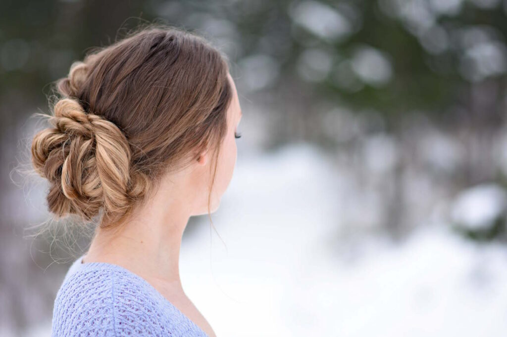 "Side view of a girl in a purple shirt, standing outside modeling a ""Stacked Fishtail Updo"" hairstyle"