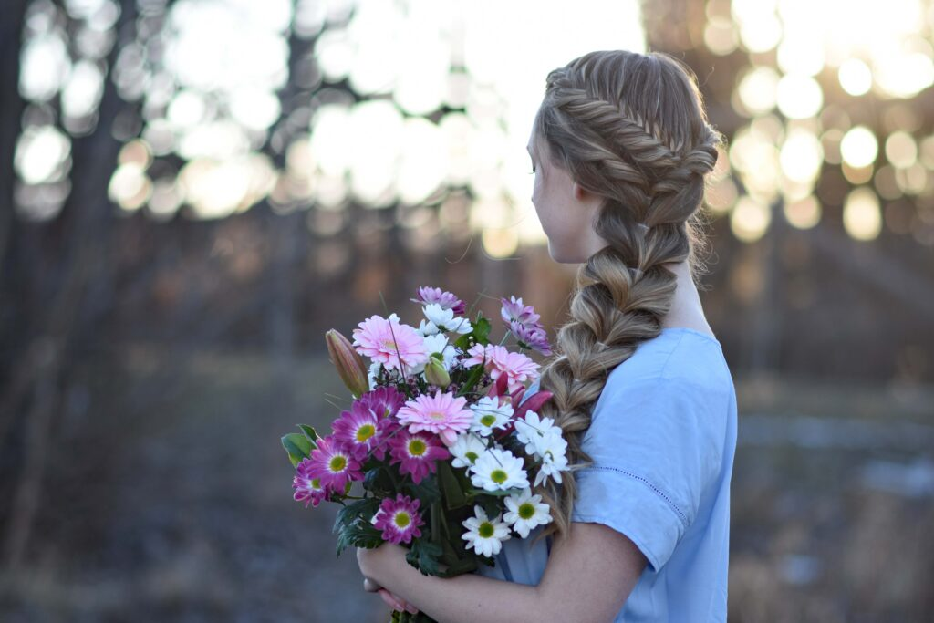 "Profile view of a young girls holding flower bouquet modeling ""Side Pull-Thru Combo"" hairstyle"
