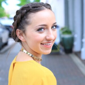 "Girl with yellow shirt standing outside modeling the "" Double Dutch Buns"" hairstyle"