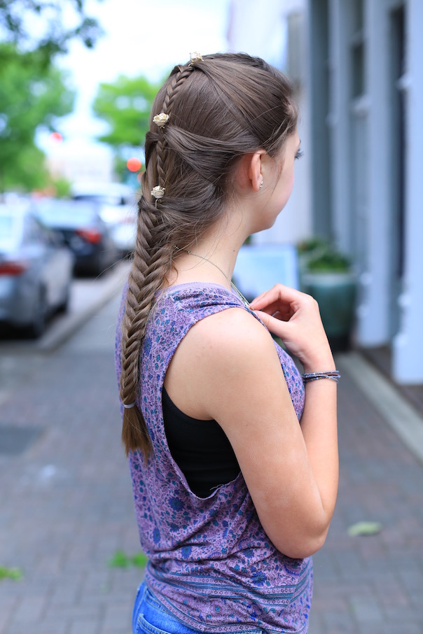 """Side view of girl standing outside with a purple shirt modeling """"Fishtail Mermaid Braid"""" hairstyle with flower accessories"""