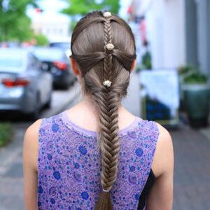 "Back view of girl standing outside with a purple shirt modeling ""Fishtail Mermaid Braid"" hairstyle with flower accessories."