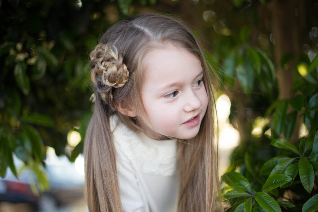 """Young girl with a white shirt playing outside and modeling """"Side Triple Flower"""" hairstyle"""