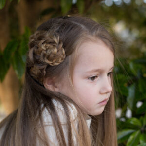 Profile of a young girl with long hair sitting outside