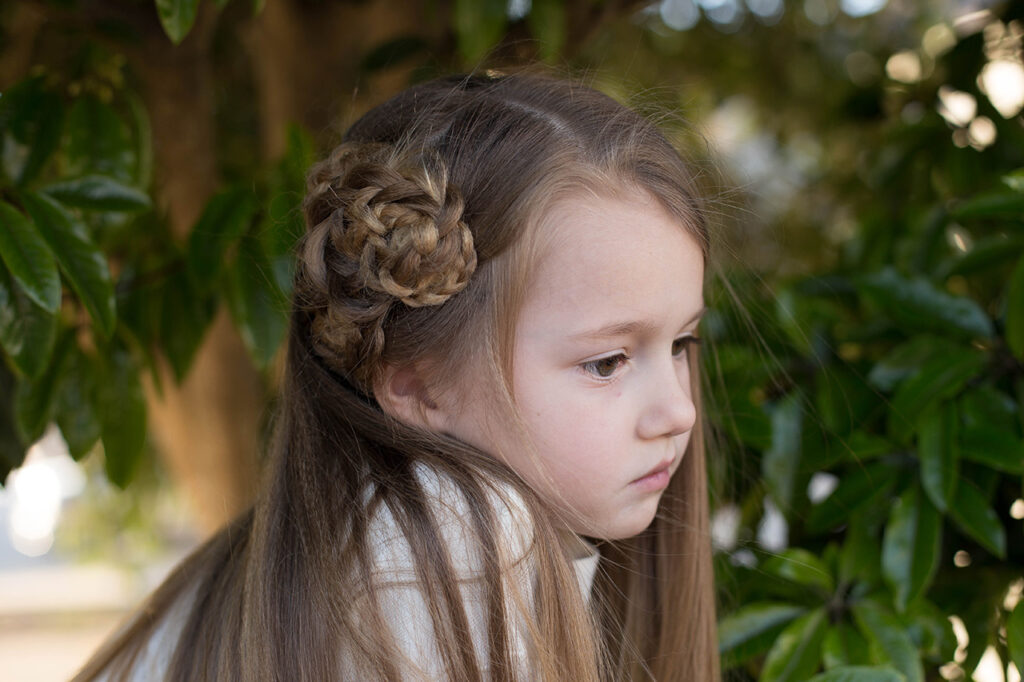 Profile of a young girl with long hair standing outside
