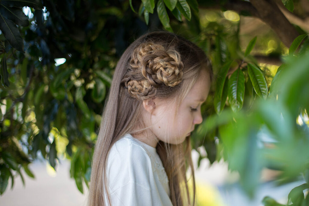 """Side view of young girl outside modeling """"Side Triple Flower"""" hairstyle"""