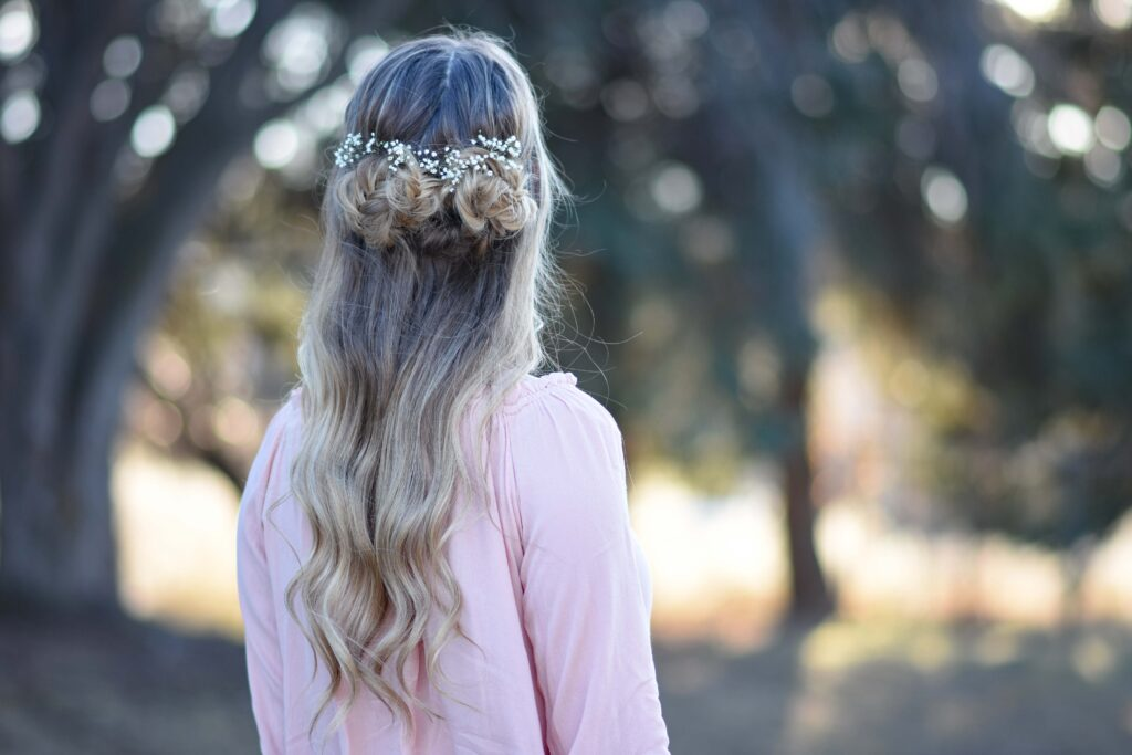 """Back view of girl wearing a pink shirt standing outside modeling """"Fishtail Half-up"""" hairstyle"""