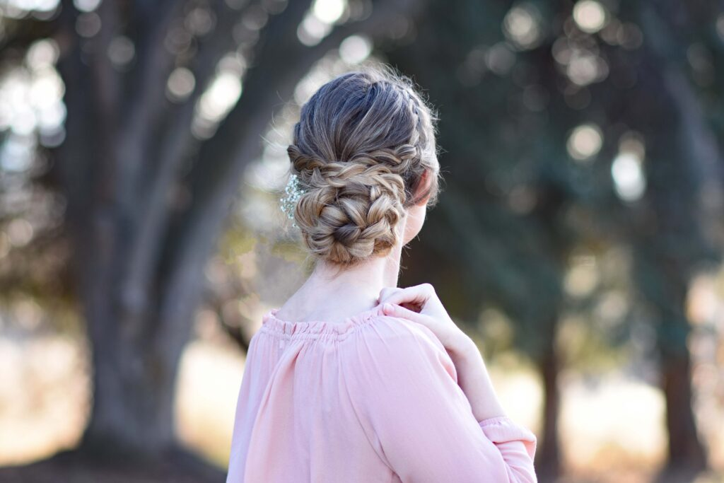 """Back view of girl wearing a pink shirt standing outside modeling """"Dutch Braided Updo"""" hairstyle"""