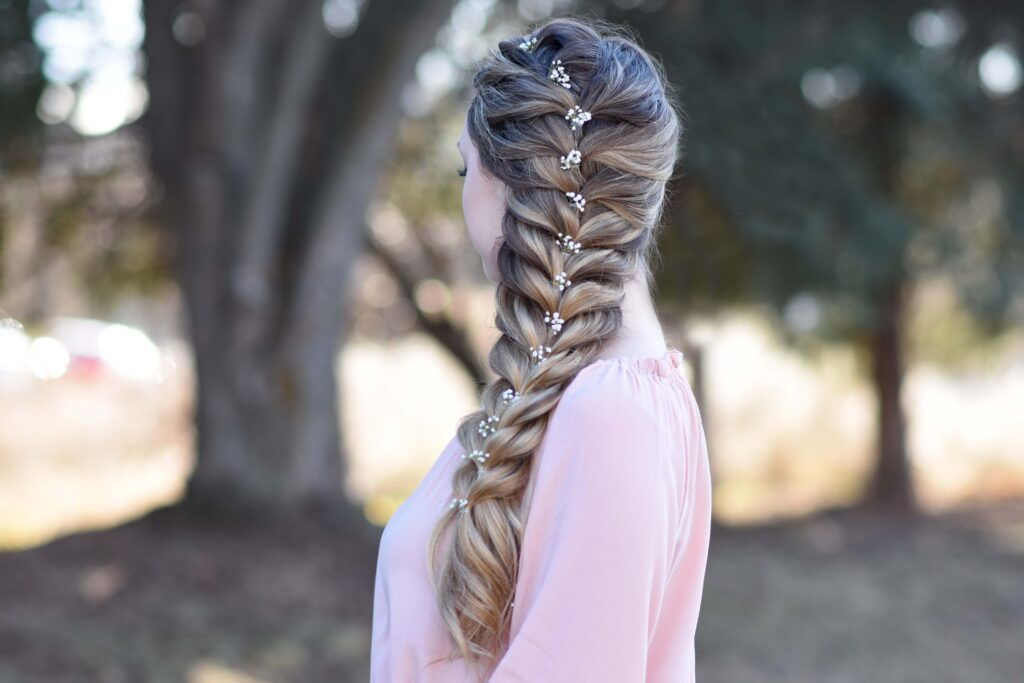 """Side view of girl wearing a pink shirt standing outside modeling """"Side Faux Braid"""" hairstyle"""