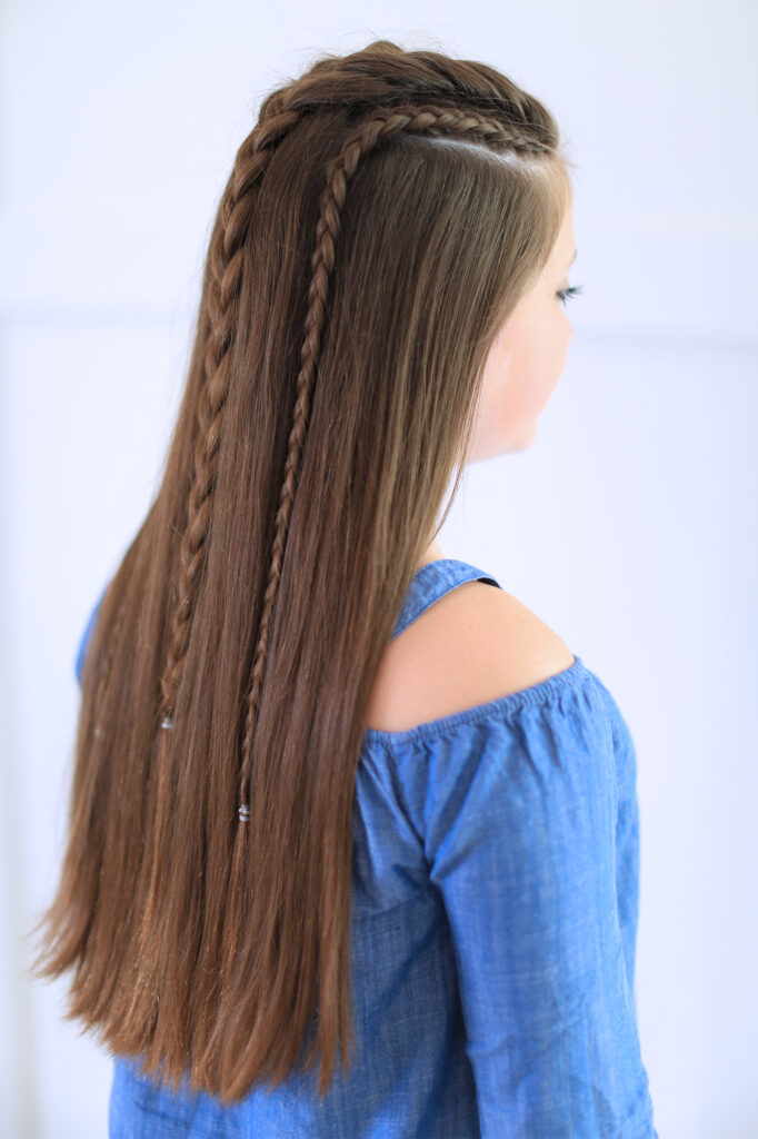 "Side back view of girl with blue shirt standing indoors modeling the ""Dutch Lace Braid Combo"" hairstyle"