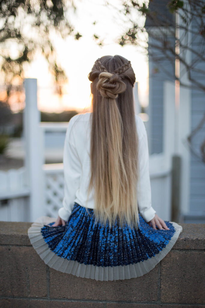 "Back view of a young girl outside modeling cute ""Braided Bun Combo"" hairstyle"
