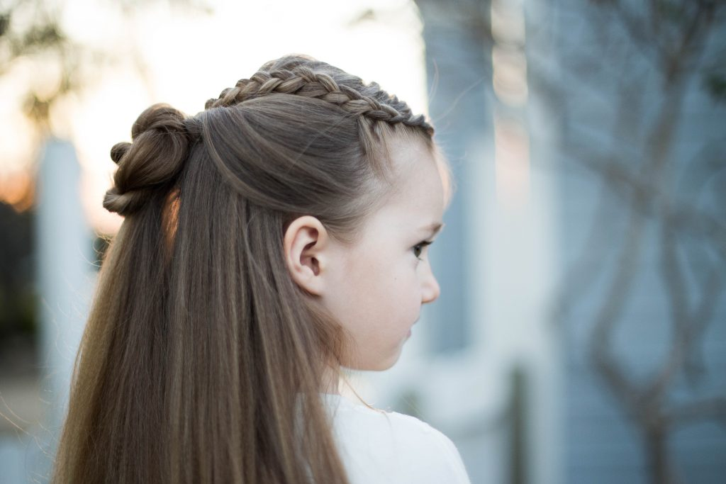 "Profile of a young girl outside modeling cute ""Braided Bun Combo"" hairstyle"
