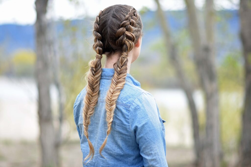 """Back view of girl wearing a blue shirt standing outside modeling """"Double Dutch Fishtails"""" hairstyle"""