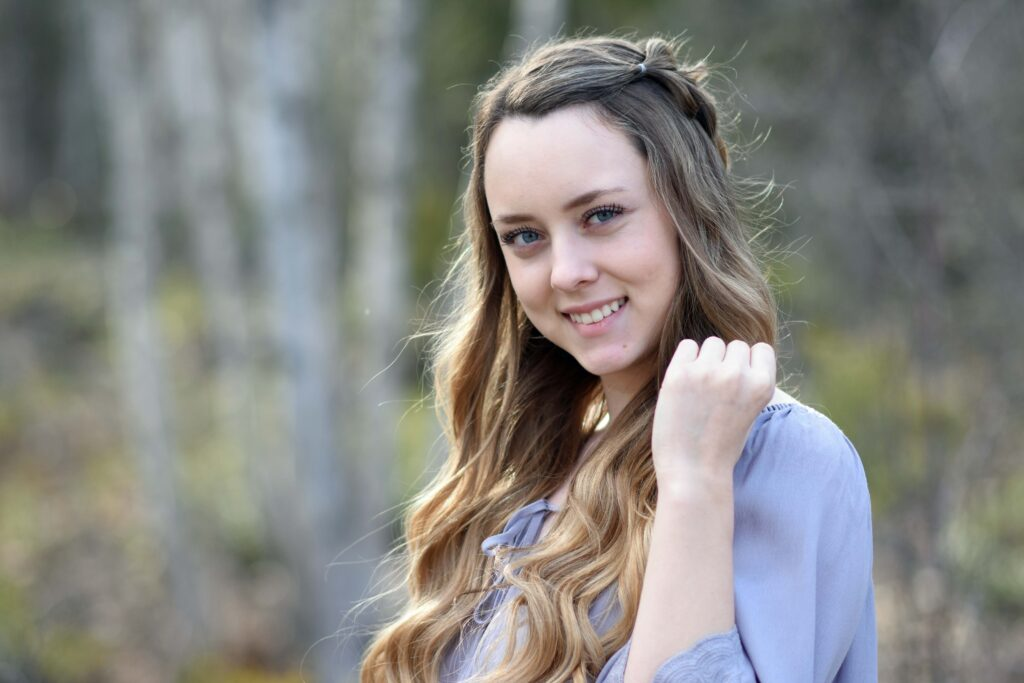 Portrait of a young girl with long hair smiling while standing in a wooded area