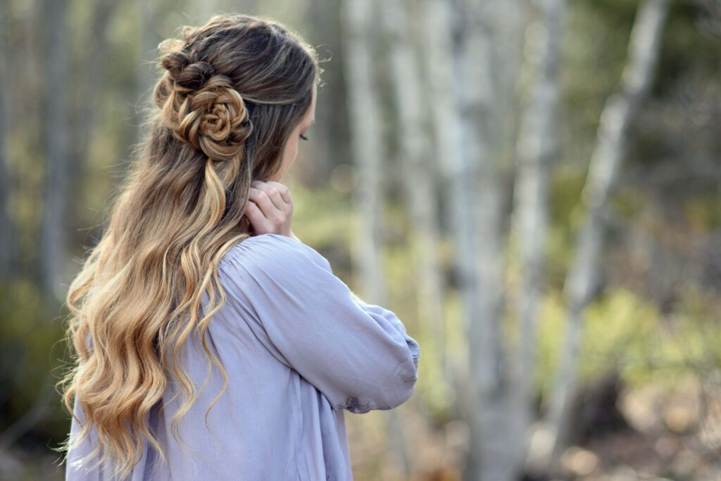 """Side view of girl standing outside in the wooded area modeling the """"Lace Pull-Thru Rosette Bun"""" hairstyle"""