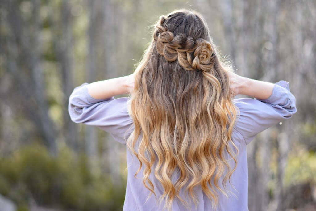 """Back view of girl standing outside in the wooded area modeling the """"Lace Pull-Thru Rosette Bun"""" hairstyle while holding her neck"""