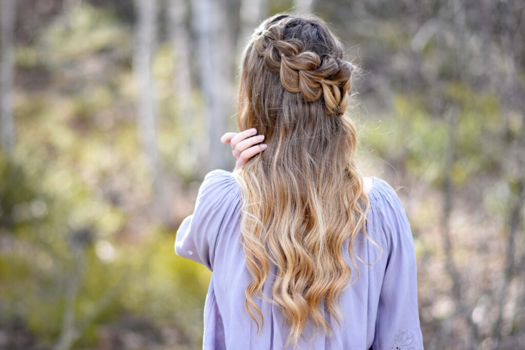 """Back view of girl standing outside in the wooded area modeling the """"Lace Pull-Thru Rosette Bun"""" hairstyle"""