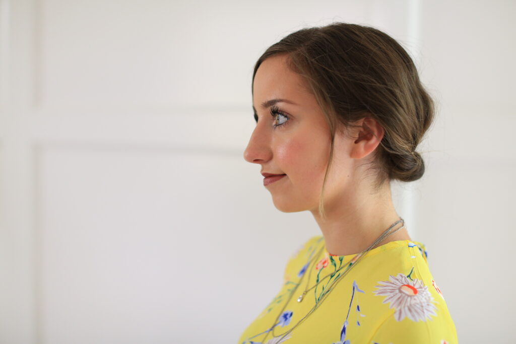 """Side view of girl standing in front of white background with a yellow shirt modeling """"Easy Rolled Updo"""" Hairstyle"""