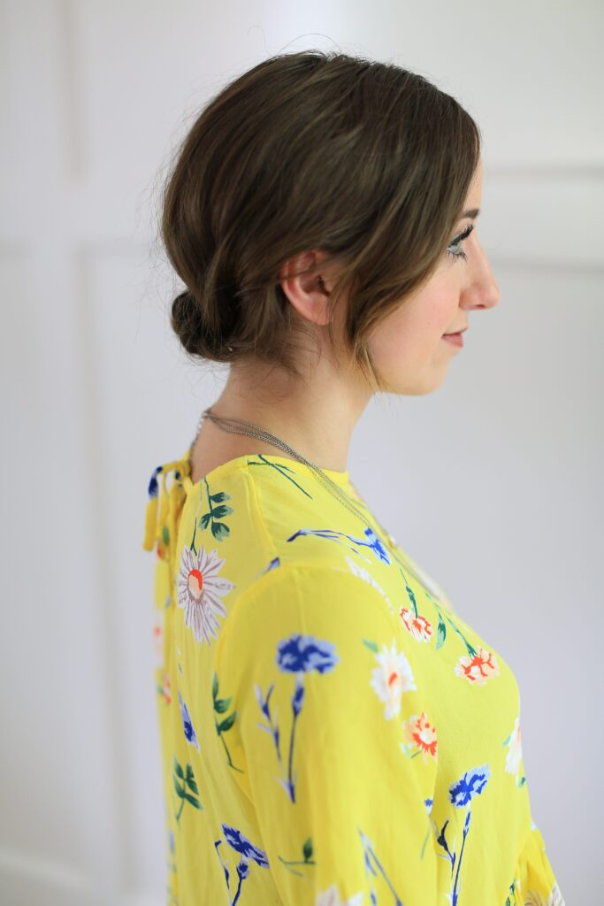 "Side view of girl standing in front of white background with a yellow shirt modeling ""Easy Rolled Updo"" Hairstyle"
