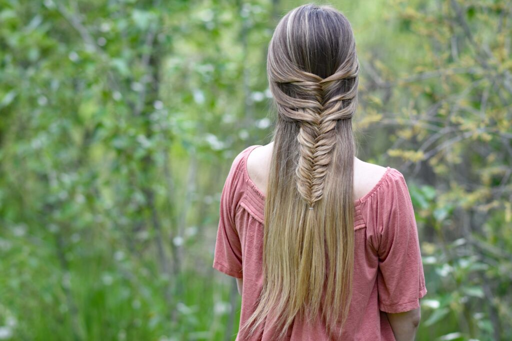 """Back view of girl with long hair standing in the wood modeling """"Mermaid Fishtail"""" hairstyle"""