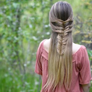 "Back view of girl with long hair standing in the wood modeling ""Mermaid Fishtail"" hairstyle"