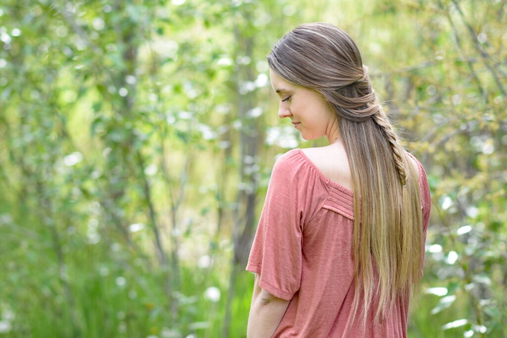 """Side view of girl with long hair standing in the wood modeling """"Mermaid Fishtail"""" hairstyle"""