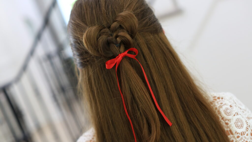 "Back view of girl standing indoors wearing a red ribbon in her hair modeling the ""Butterfly Tieback"" hairstyle"
