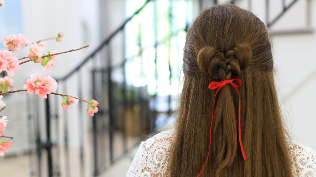 "Close up back view of girl standing indoors wearing a red ribbon in her hair modeling the ""Butterfly Tieback"" hairstyle"