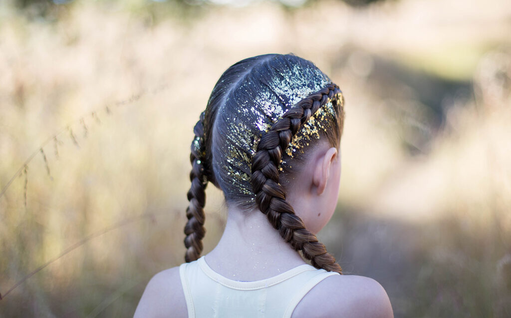 "Back view of girl outside with gold glitter in her hair modeling ""Dutch Glitter Braids"" hairstyle"