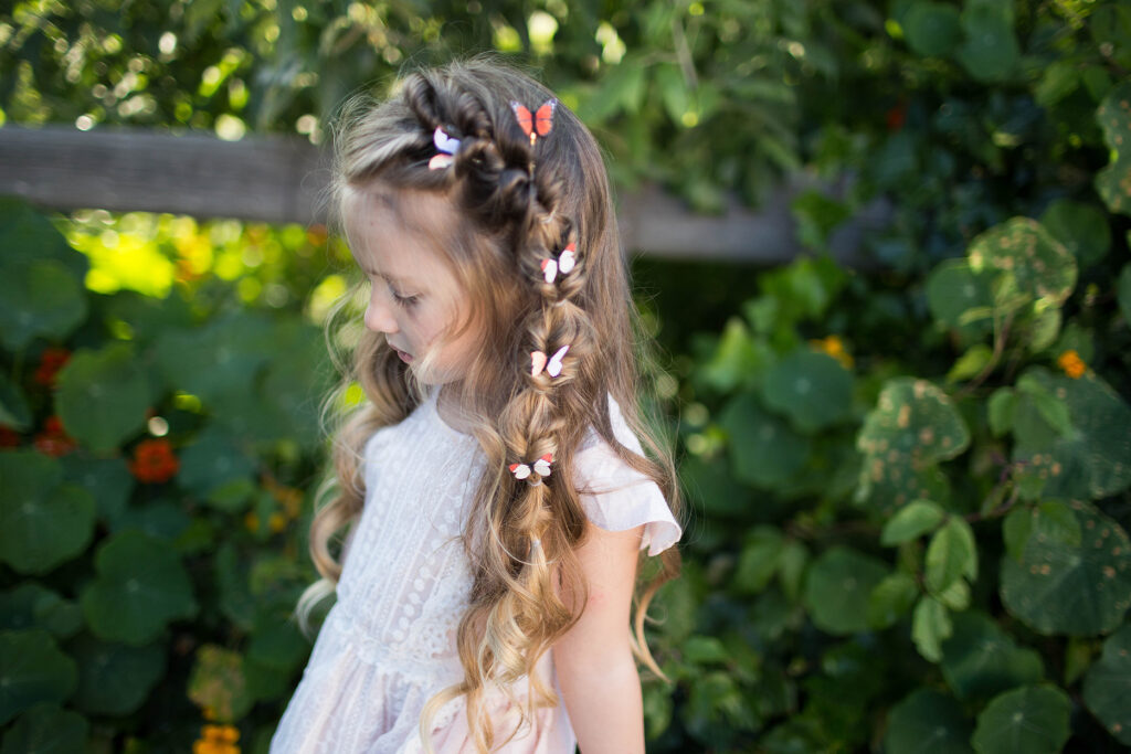 "Side view of a young girl with hair standing outside modeling ""Flip Faux Fishtail"" hairstyle with butterfly accessories"