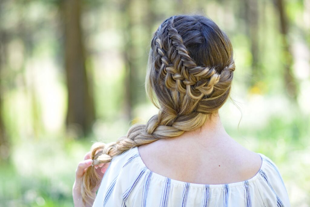 """Back view of a young girl with long hair with a striped shirt standing outside modeling """"Double Dutch Side Braid"""" hairstyle"""