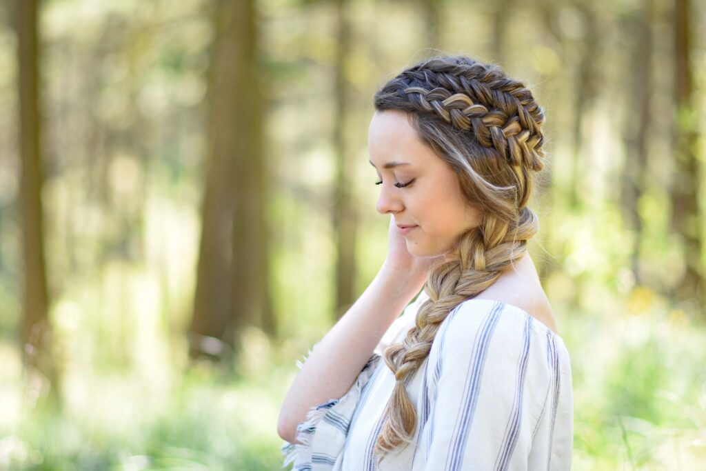 """Profile view of a young girl with long hair standing outside modeling """"Double Dutch Side Braid"""" hairstyle"""
