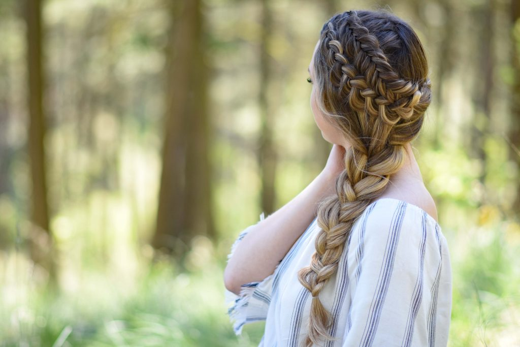 """Side view of a young girl with long hair with a striped shirt standing outside modeling """"Double Dutch Side Braid"""" hairstyle"""