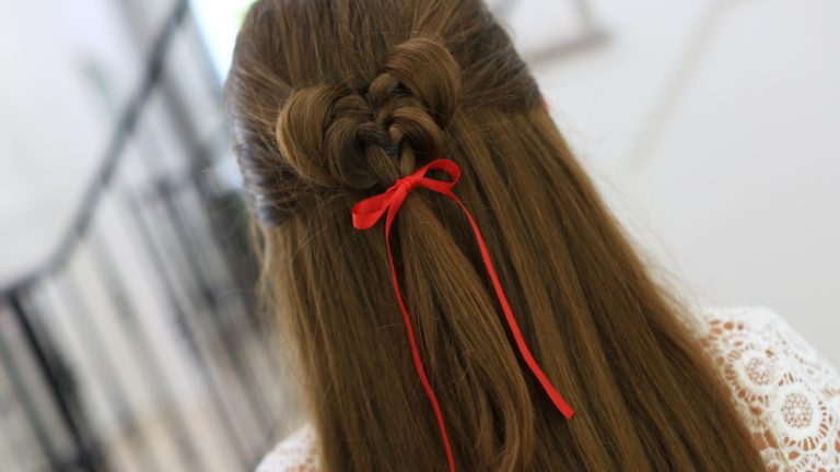 """Back view of girl standing indoors wearing a red ribbon in her hair modeling the """"Butterfly Tieback"""" hairstyle."""