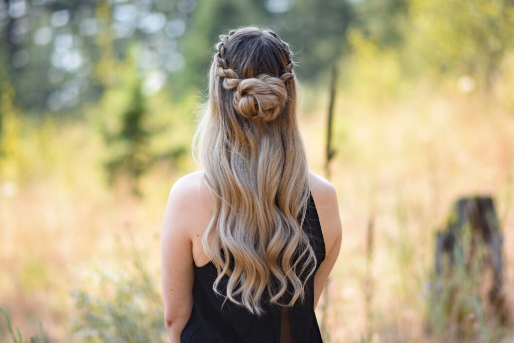 """Back view of a young girl wearing a black shirt standing in the meadow modeling """"Half-Up Rope Twist Bun"""" hairstyle"""