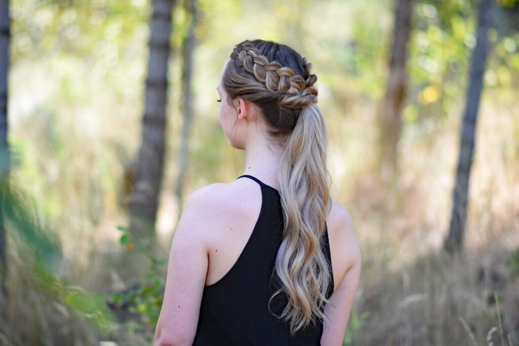 """Side view of a young girl wearing a black shirt standing in the meadow modeling """"Twisted Dutch Braid Ponytail"""" hairstyle"""