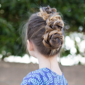 "Side view of a little girl with long hair standing outside modeling ""Triple Bun Updo"" hairstyle"