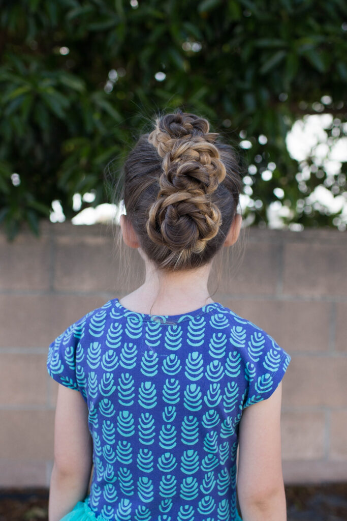 """Back view of a little girl with long hair standing outside modeling """"Triple Bun Updo"""" hairstyle"""